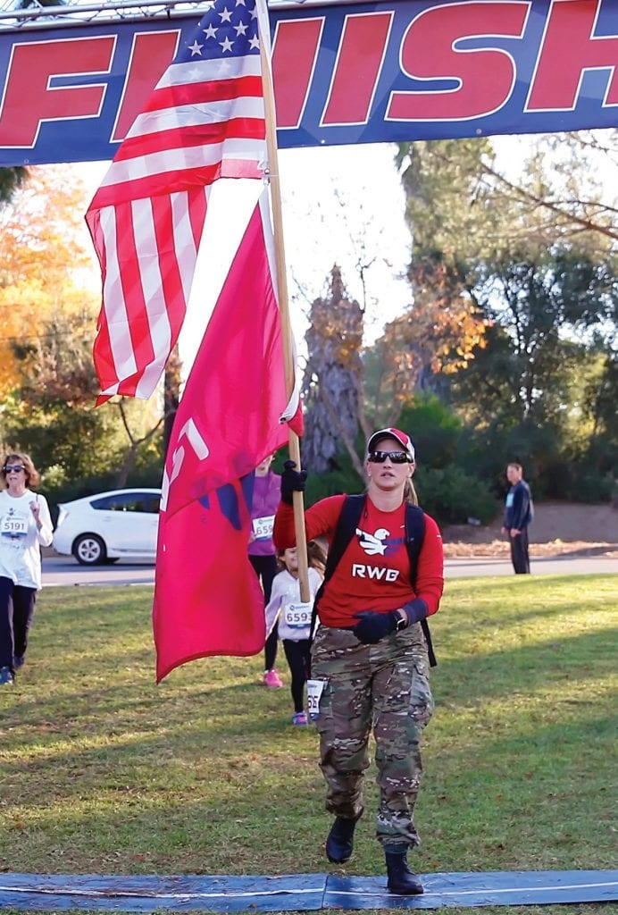 GLORIOUS FINISH—Above, Jaclyn Pieper of Thousand Oaks, walking for her friend, Marine Corps veteran Dan Manrique, who died trying to save lives at Borderline, carries Old Glory across thefinish line.