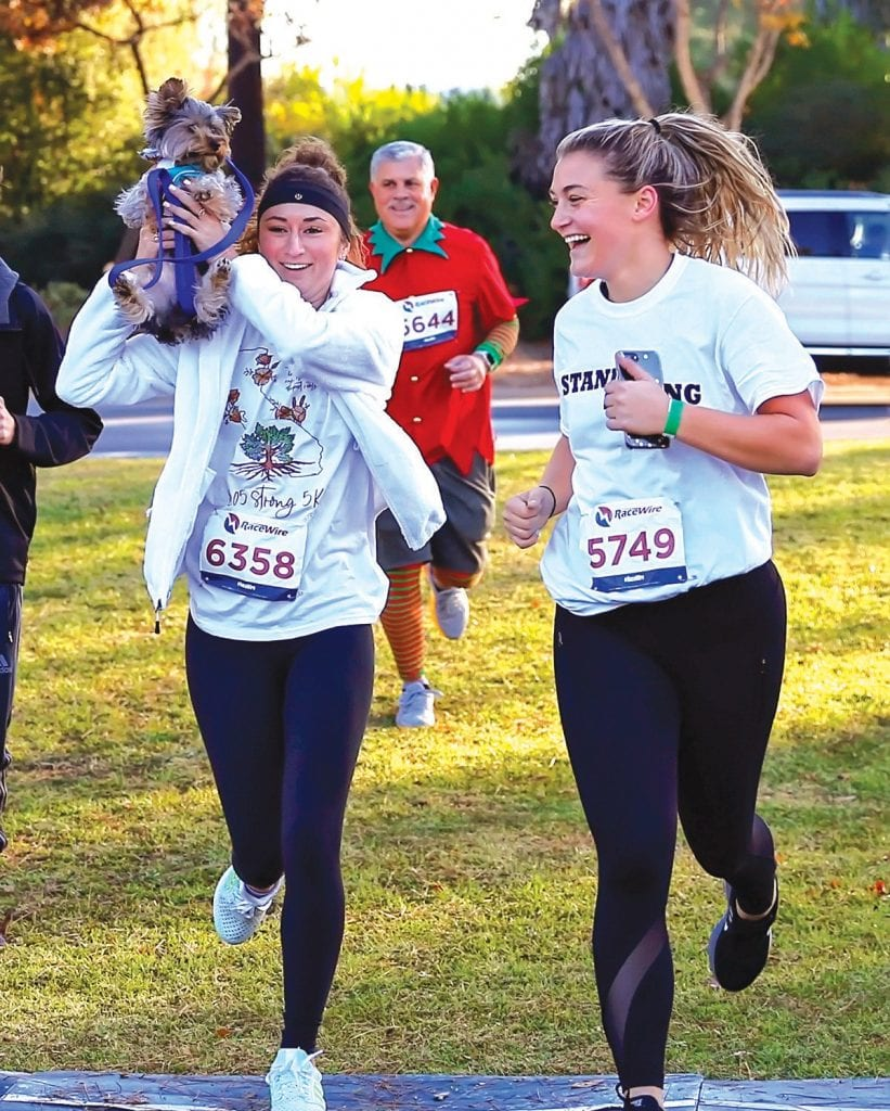 At right, friends Alyssa Frank and Jordan Jeworski reach thefinish with their canine friend Zuma.
