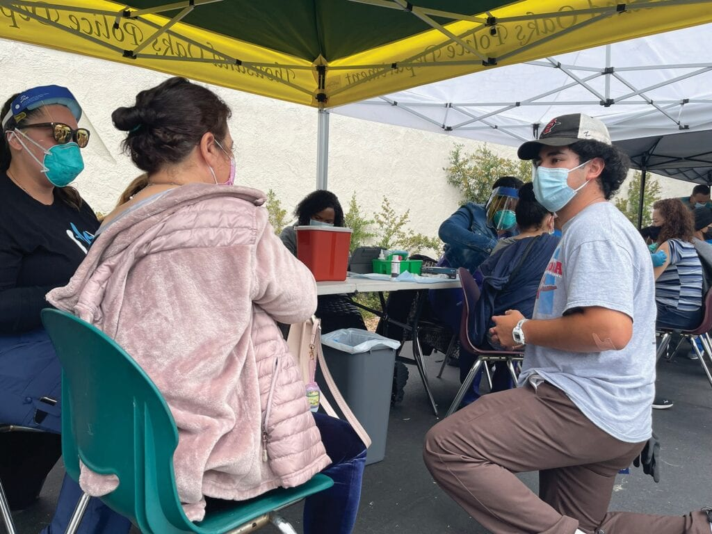 CONVEYING INFORMATION—Sebastian Pacheco, right, offers translation services during a May 15 vaccine clinic in the Las Casitas neighborhood of Newbury Park. The 19-year-old grew up on Warwick Avenue and now works for CRPD and Amazon. Courtesy photo